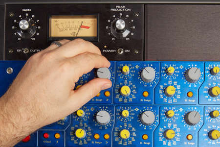 fader: Hand of man is turning knobs on an audio effects deck. Stock Photo