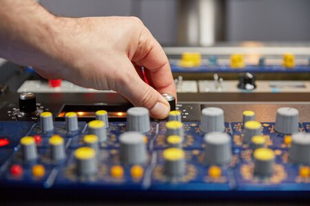 fader: Knobs and faders on a mixing console with hand of the audio engineer.