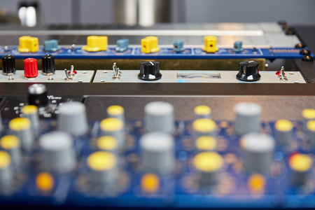 knobs: Knobs and faders on a mixing console with blurred foreground. Stock Photo