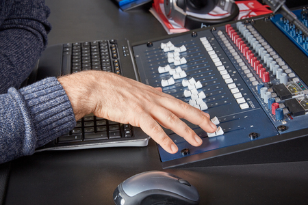 radio dj: Male audio engineer moving the sliders on a mixing deck in a professional sound studio