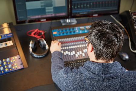 サウンド エンジニアは録音スタジオのミキシング コンソールに取り組んで