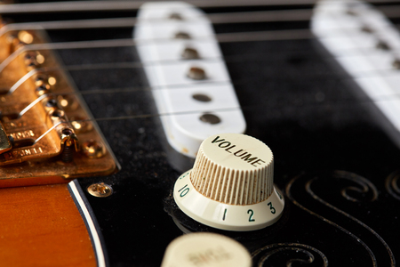 volume knob: Detail of volume knob and string of a vintage electric guitar Stock Photo
