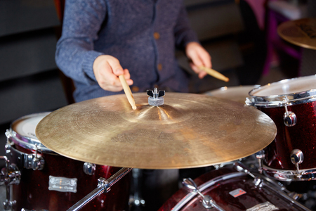 The drummer ist striking the cymbal with the drumstick