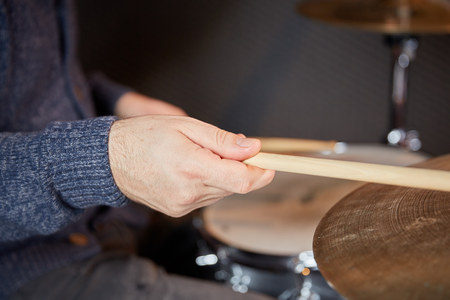 cymbal: Hand of a drummer that holds a drumstick and plays the cymbal