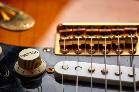 volume knob: Detail view of the volume knob next to the strings of a vintage electric guitar
