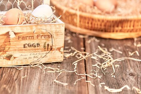 egg box: Eggs in an wooden egg box on a wooden talbe with nest in background Stock Photo
