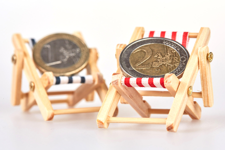 deckchair: Two euro coins on a blue and a red deckchair isolated on white background