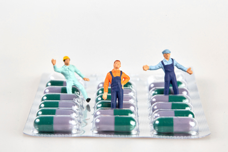 blister package: Little figurine people on a medicine pill blister package.