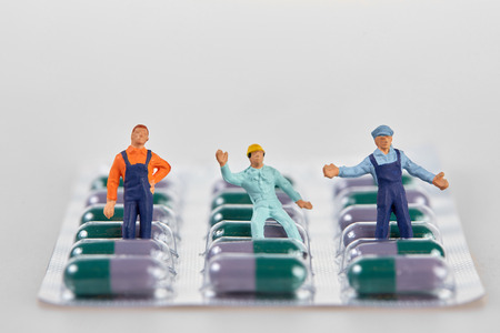 Miniature people placed on blister package with medical pills