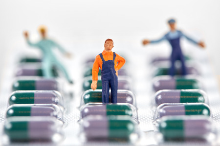 humane: Miniature working men standing on package of medical pills Stock Photo