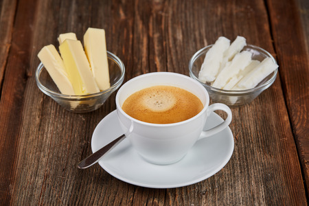 bulletproof: Coffee, butter and coconut oil for bulletproof coffee on a brown wooden table Stock Photo