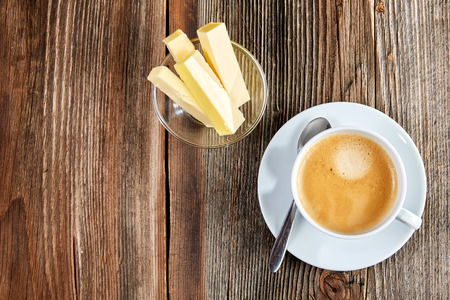 bulletproof: Bulletproof coffee in white cup with butter and coconut oil on a wooden table Stock Photo