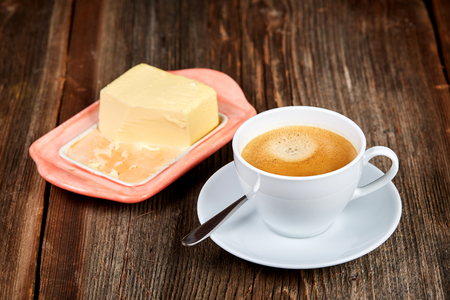 Coffe and butter on a dish on a brown wooden table Stock Photo