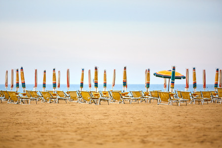 lounges: Empty sun lounges and all closed but one open parasols on the beach