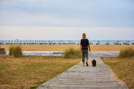 havanese: Woman walking to the beach with a black havanese dog on the lead Stock Photo