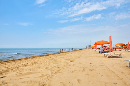 lounges: Beach in italy with parasols and sun lounges under a blue sky