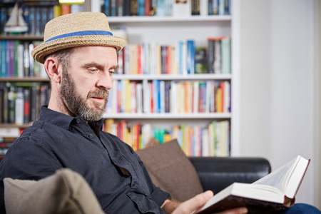 prime adult: Student with hat sitting in front of a book shelf reading a book