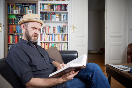 prime adult: Man with beard reading a book in his living room on a leather couch