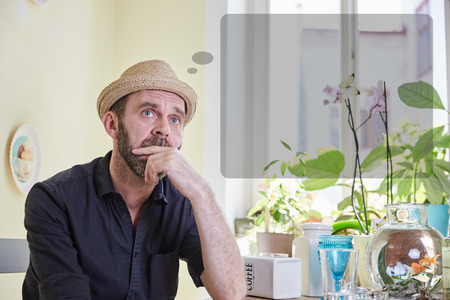 musing: Man musing with a thought bubble over his head sitting in a kitchen indoors