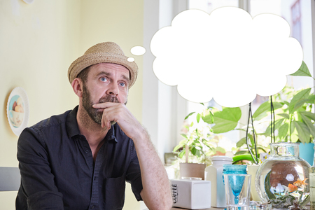 brooding: Man brooding with a thought bubble over his head sitting in a kitchen indoors Stock Photo