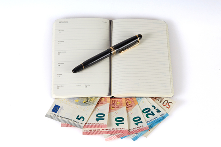 chequera: Ganar dinero con la escritura simbolizado con la pluma y el cuaderno en billetes de dinero en euros Foto de archivo