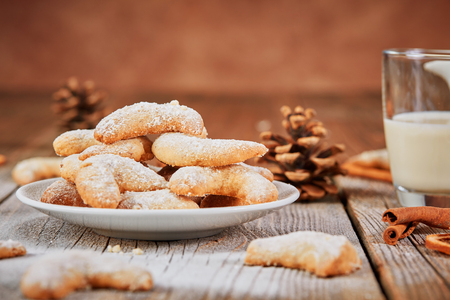 Vanillekipferl with powder sugar on wooden table with glass of milk and cinnamon rolls Stock Photo - 66555196
