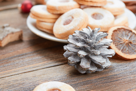 Pile of cookies on white plate on a wooden table and a white pine cone