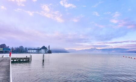 Lake Attersee in the morning with Schloss Kammer and a jetty for boats