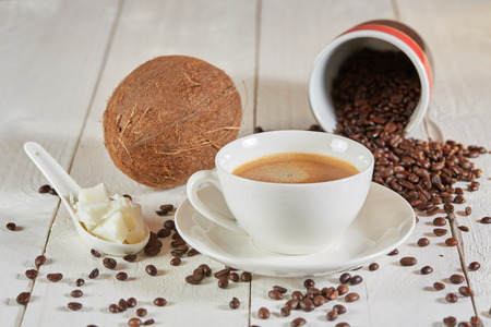 Bulletproof coffee and coconut and beans on white table Stock Photo - 69672127