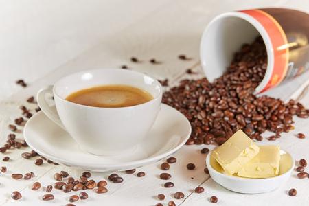 Café a prueba de balas con mantequilla y frijoles en la mesa blanca Foto de archivo