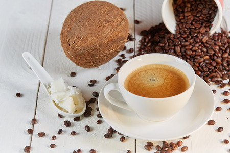 bullet proof: Coffee beans and coconut on white table for bulletproof coffee