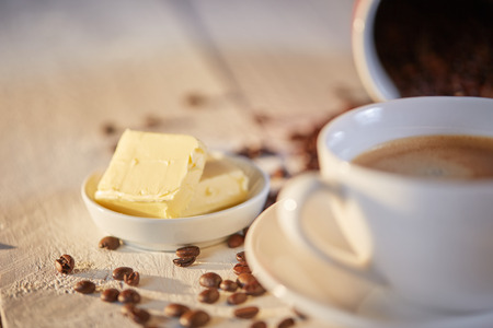 Macro shot of butter for bulletproof coffee with beans on white table Stock Photo