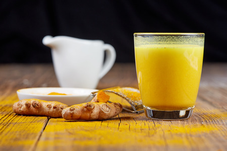 Turmeric tea golden milk with orange curcuma root on wooden table 免版税图像