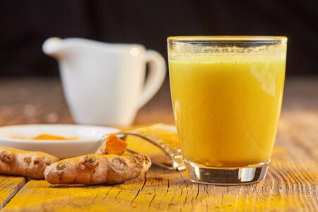 Curcuma root for golden milk on brown wooden table