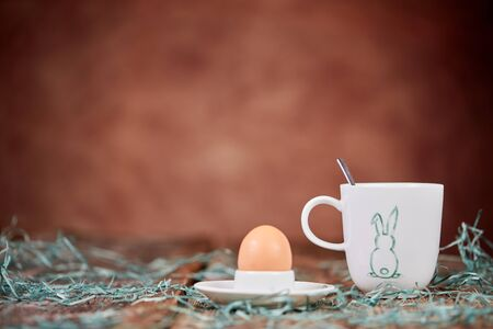 Egg in eggcup and cup of coffee for easter breakfast with green grass on brown wooden table