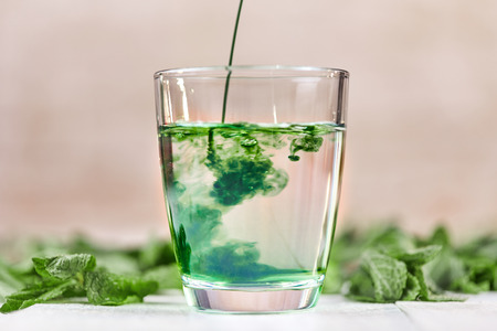 Dissolving liquid chlorophyll in glass of water on white table with green mint Stock Photo