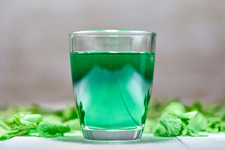 Intensive green shining mint drink on white table with mint leaves on white table