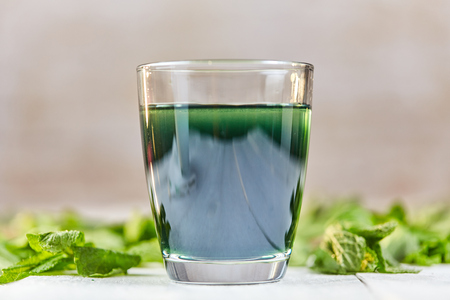 Green chlorophyll drink in glass with water on white table with green mint Stock Photo