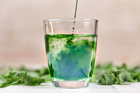 Green chlorophyll drink in glass with water on white table with green mint Reklamní fotografie
