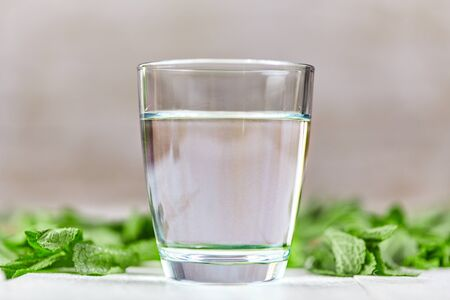 Fresh glass of water with green mint on white table