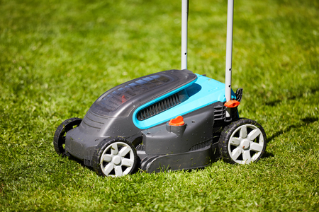 Lawn mower in the garden after mowing in the grass