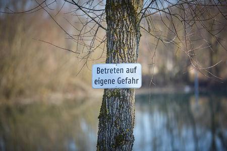lake with warning Betreten auf eigene Gefahr Stock Photo