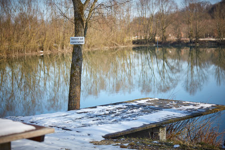 lake with warning Betreten auf eigene Gefahr Stock Photo - 126328955