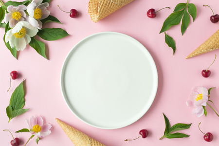 Flatlay of cerry, sweet cones and peonies over pastel pink background. Top view with space for your text Фото со стока