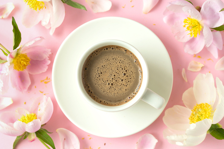 Spring or summer morning concept. Flat-lay of coffee and flowers over light pink background, top view with space for your text