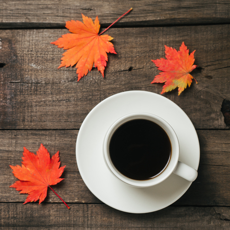 Autumn leaves and a cup of coffee with plaid on old vintage wooden background.