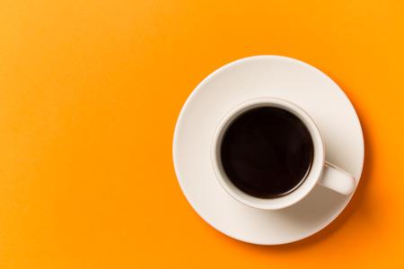 Een kopje koffie geïsoleerd op oranje. Bovenaanzicht.