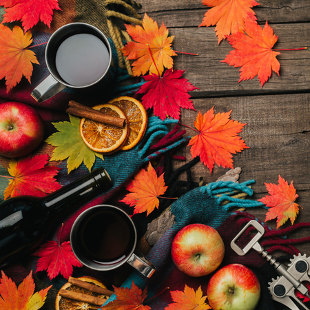 Autumn leaves, two cups of wine, red apples with plaid on old vintage wooden background.