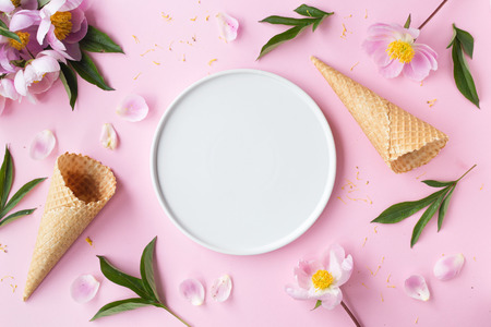 Spring or summer mood concept. Flat-lay of waffle sweet cone with berryy over pastel light pink background, top view Фото со стока