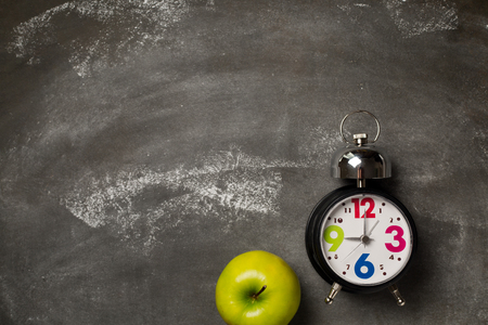 Round vintage clock and apple on grey background. School concept. Copy space. Top view. Flat lay